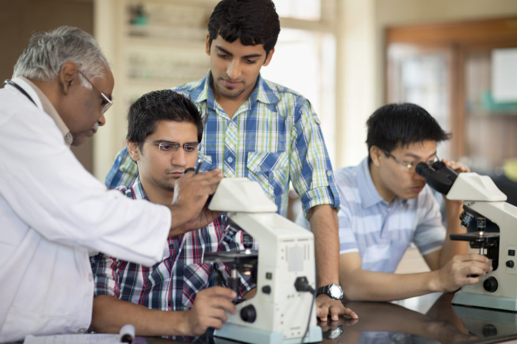 Portrait Of Students Looking Through Microscope
